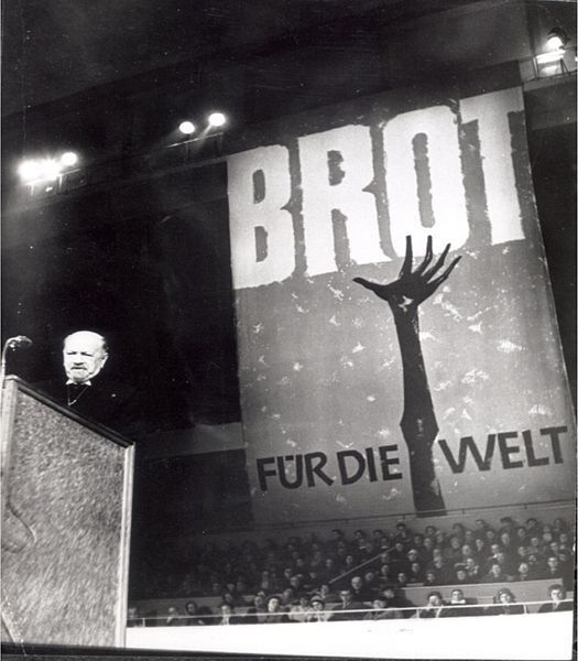 "Eröffnung der ersten Aktion ""Brot für die Welt"" in Berlin am 12. Dezember 1959, Quelle: [http://commons.wikimedia.org/wiki/File:Er%C3%B6ffnung_Erste_Aktion.jpg?uselang=de Wikimedia Commons] ([https://creativecommons.org/licenses/by-sa/3.0/deed.de CC BY-SA 3.0])."