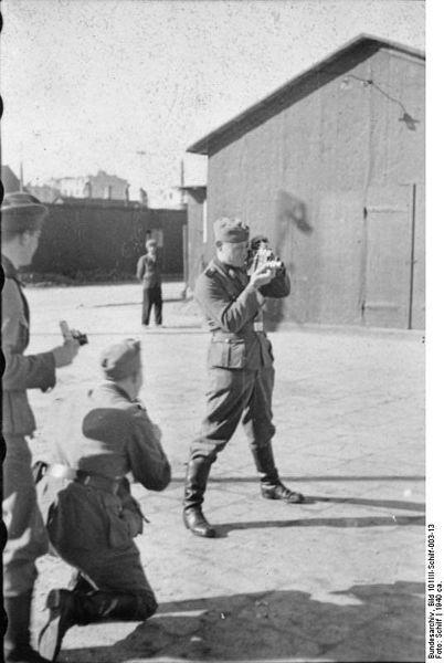 Ghetto Litzmannstadt, Polen, 1940: SS-Soldat einer Propaganda-Kompanie (PK-Filmberichter) bei der Aufnahme mit einer Filmkamera. Fotograf: Schilf, Quelle: [http://commons.wikimedia.org/wiki/File:Bundesarchiv_Bild_101III-Schilf-003-13,_Polen,_Ghetto_Litzmannstadt,_PK-Filmberichter.jpg?uselang=de. Wikimedia Commons/Bundesarchiv, Bild 101III-Schilf-003-13] ([https://creativecommons.org/licenses/by-sa/3.0/de/deed.en CC BY-SA 3.0 DE]).
