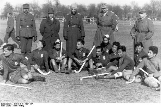 Hockeyspiel einer indischen gegen eine deutsche Wehrmachtsmannschaft, Frankreich, Atlantikwall, Stadion Bordeaux, 21. März 1944. Foto: Wette. Quelle: [https://commons.wikimedia.org/wiki/File:Bundesarchiv_Bild_101I-264-1604-05A,_Bordeaux,_Hockeyspiel_Wehrmachtsangeh%C3%B6riger.jpg?uselang=de Wikipedia / Bundesarchiv Bild 101l-264-1604-05A] ([https://creativecommons.org/licenses/by-sa/3.0/de/deed.de CC BY-SA 3.0 DE])