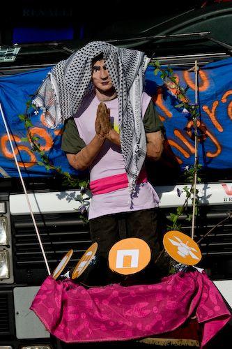 """""""San Precario"""", Mayday 2008 – Die Mayday-Bewegung erfand einen Schutzheiligen für Prekarisierte: """"San Precario"""". Seine Insignien verweisen auf einige Facetten der Prekarisierung: Einkommen, Unterkunft, Gesundheit, Kommunikation und Transportmittel, Foto: Neddo is a Zombie, Mai 2008, Mailand, Italien, Quelle ([https://creativecommons.org/licenses/by/2.0/ CC BY 2.0]): [http://www.flickr.com/photos/n3ddo/2469136600 Flickr]"""