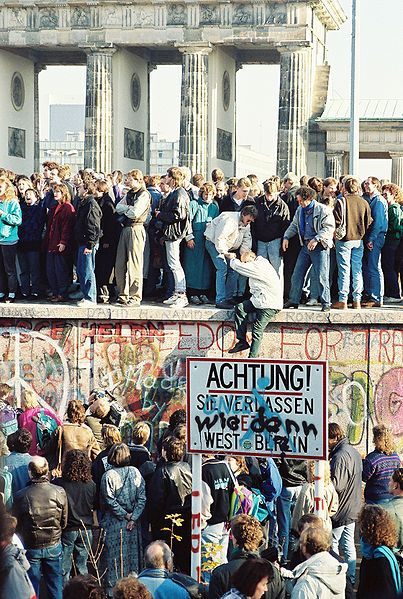 """9. November 1989: Menschen auf der Berliner Mauer vor dem Brandenburger Tor. Die Aufschrift auf dem Schild: """"Achtung! Sie verlassen jetzt West-Berlin"""" wurde übersprüht mit der Frage """"Wie denn?"""". Fotograf: Sue Ream (San Francisco, California), Quelle ([https://creativecommons.org/licenses/by/3.0/deed.en CC BY 3.0]): [http://commons.wikimedia.org/wiki/File:BerlinWall-BrandenburgGate.jpg Wikimedia Commons]."""