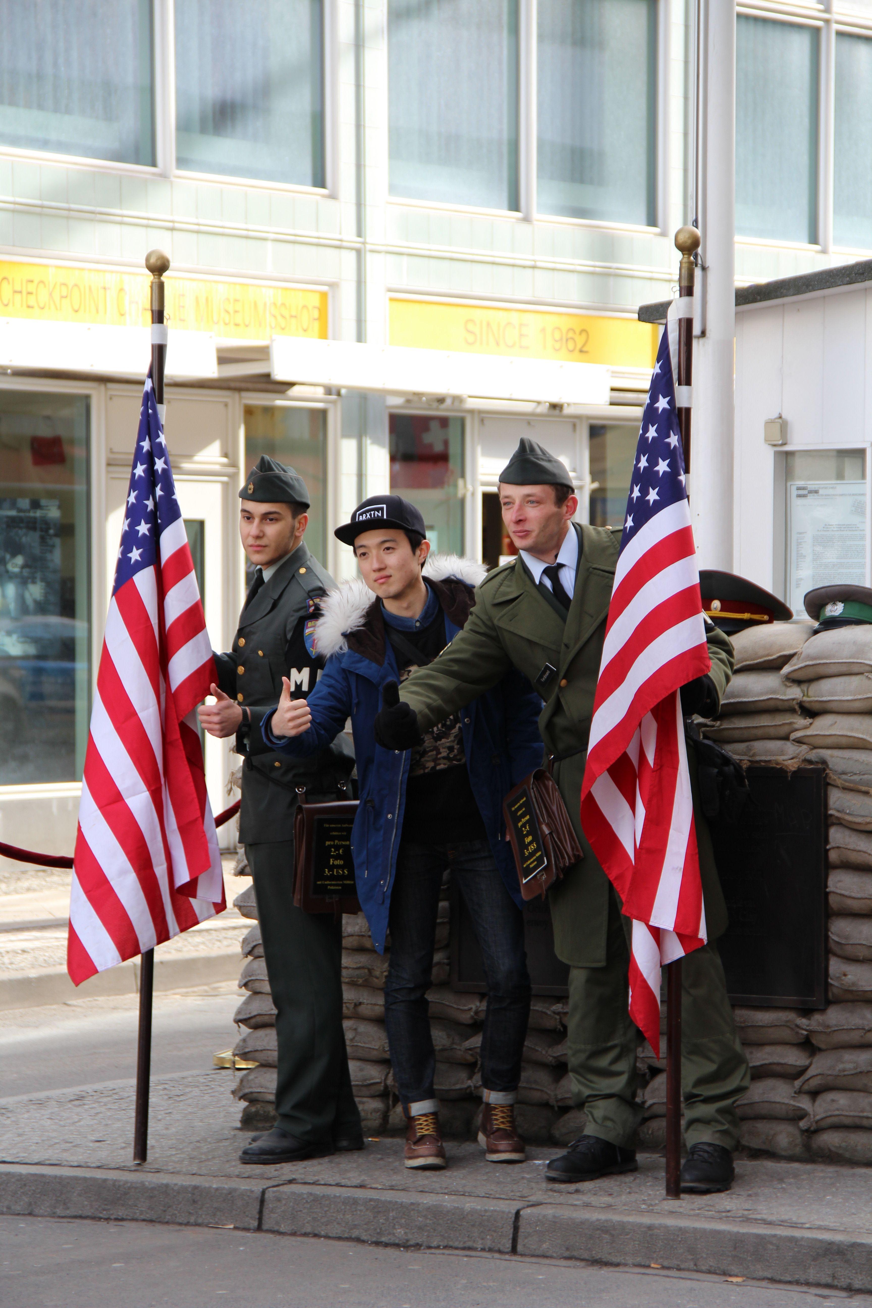 """Checkpoint-Charlie, Foto: Achim Saupe, Berlin, 8.2.2014, Lizenz: [https://creativecommons.org/licenses/by-nc/3.0/de/ CC BY-NC 3.0 DE]<br /> Zeithistorisches Reenactment und Touristenattraktion am Checkpoint-Charlie. Eingerahmt zwischen Schauspieler, zielt hier die Authentizitätssuggestion auf Erleben und Event am """"historischen Ort"""". Auch wenn es sich freilich um eine Rekonstruktion handelt."""
