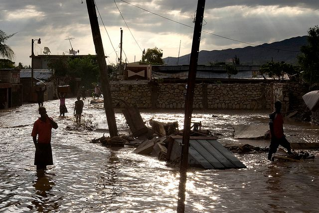 "Naturkatastrophen: Tropische Stürme und Überschwemmungen. Haiti, 9. September 2008. ""Tropical Storm Hanna Floods Gonaives. People walk through the flooded streets of Gonaives, Haiti. 8 days after tropical storm Hanna swept through the area."" Photo ID 192484. 09/09/2008. Gonaives, Haiti. Quelle: [https://www.unmultimedia.org/photo/ UN Photo Logan Abassi] / [https://www.flickr.com/photos/un_photo/5479976200/ Flickr] ([https://creativecommons.org/licenses/by-nc-nd/2.0/ CC BY-NC-ND 2.0])."