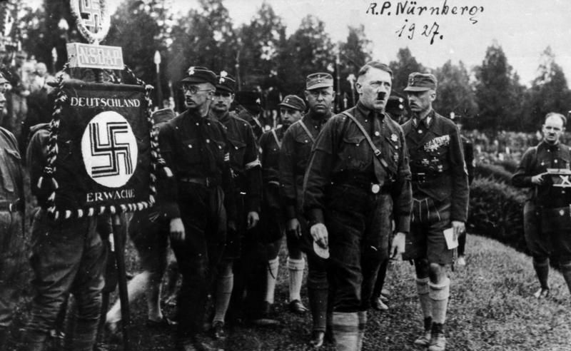 Rally of the Nazi Party in Nuremberg 1927, from right: Franz Pfeffer von Salomon [Franz von Pfeffer], Adolf Hitler, Gregor Strasser, Rudolf Hess, Heinrich Himmler; on the right the SA banner. Photographer unknown, Source: [https://commons.wikimedia.org/wiki/Category:Sturmabteilung?uselang=de#/media/File:Bundesarchiv_Bild_146-1969-054-53A,_N%C3%BCrnberg,_Reichsparteitag.jpg Wikimedia Commons] / Bundesarchiv Bild 146-1969-054-53A ([https://creativecommons.org/licenses/by-sa/3.0/de/deed.de CC-BY-SA 3.0]).