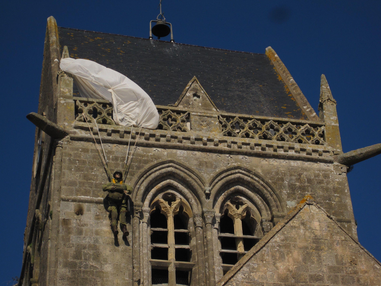 Eine andere Form der öffentlichen Geschichtsrepräsentation stellt diese Fallschirmspringer-Puppe am Turm der Kirche von Sainte-Mère-Église in der Normandie in Frankreich dar. Sie soll an einen amerikanischen Soldaten erinnern, der bei der alliierten Invasion 1944 versehentlich an diesem Kirchturm hängenblieb. Dieser eher spielerische Zugang zeigt einen relativ ungezwungenen Umgang mit Geschichte, wirkt die Puppe doch fast wie eine Werbemaßnahme für das gegenüber der Kirche stehende Airborne Museum.  Foto: Irmgard Zündorf, Sainte-Mère-Église 2015, Lizenz: [https://creativecommons.org/licenses/by-nc/3.0/de/ CC BY-NC 3.0 DE]