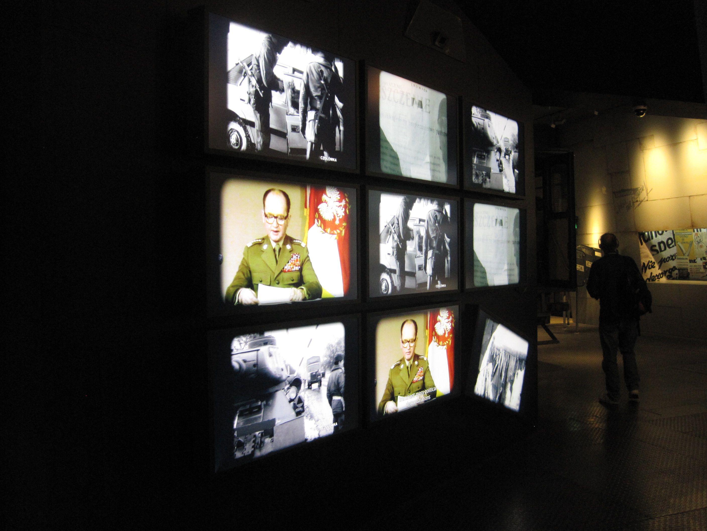 Multimedia-Einsatz in Museen bietet sich immer dann an, wenn die zu präsentierenden Objekte medialer Art sind. In diesem Fall zeigen die verschiedenen Bildschirme einerseits die Fernsehansprache General Jaruzelskis vom 13. Dezember 1981, in der er die Einführung des Kriegsrechts in Polen verkündete, und andererseits bereits die Auswirkungen des Kriegsrechts. Foto: Irmgard Zündorf, Europäisches Solidarność-Zentrum (Polnisch: Europejskie Centrum Solidarności), Danzig 2015, Lizenz: [https://creativecommons.org/licenses/by-nc/3.0/de/ CC BY-NC 3.0 DE]