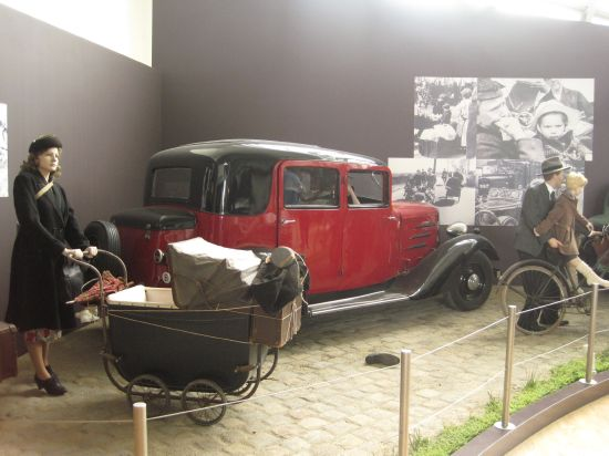 History is enacted here with the help of historical objects and mannequins. These are presented opposite historical photos, some of which show images similar to the street scenes enacted here, thereby authenticating them. Photo: Irmgard Zündorf, Military Historical Museum, Brussels 2015, License: [https://creativecommons.org/licenses/by-nc/3.0/de/ CC BY-NC 3.0 DE]