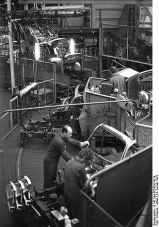 VW-Werk, Wolfsburg, Karosseriemontage, 23. Januar 1973, Foto: Lothar Schaack. Quelle: [https://commons.wikimedia.org/wiki/File:Bundesarchiv_B_145_Bild-F038793-0019,_Wolfsburg,_VW_Autowerk.jpg Wikimedia Commons / Presse- und Informationsamt der Bundesregierung - Bildbestand (B 145 Bild)] [https://creativecommons.org/licenses/by-sa/3.0/de/deed.en CC BY-SA 3.0 DE]