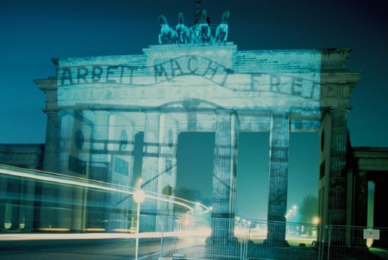 """""""Die Tore der Deutschen"""" – Am 27. Januar 1997 projizierte Horst Hoheisel zwei verschiedene Fotos des Auschwitz-Tores mit dem Satz """"ARBEIT MACHT FREI"""" auf das Brandenburger Tor. Ein historisches Schwarz-Weiß-Foto mit dem verschlossenen Tor aus der Zeit des KZ und ein Farbfoto des geöffneten Tores aus der heutigen Zeit. """"Auch nach der Wiedervereinigung"""", so gab der Künstler damals zu bedenken, """"kann das Brandenburger Tor nicht das Symbol ungebrochener nationaler Identität und historischer Kontinuität sein."""" Foto: Horst Hoheisel © mit freundlicher Genehmigung"""