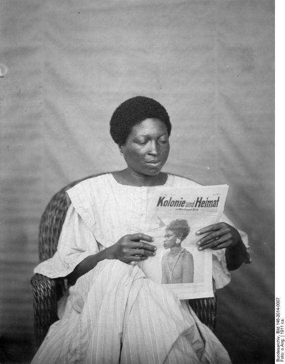 The illustrated magazine Kolonie und Heimat (Colony and Homeland) was the official publication of the Women's League of the German Colonial Society. Its aim was to popularize the colonies in Germany and make them attractive as settlement areas. The African woman in a wicker chair and European reform clothing stands in contrast to the image on the magazine she's holding in her hands, but suggests the possibility of Heimat in the colonies. The picture must have been disconcerting at the time, since Heimat was hardly associated with people living in the colonies, much less with African women displaying a dignified and sophisticated middle-class domesticity. <br /> Kolonie und Heimat ca. 1911, b/w photograph 18 x 18 cm. The woman's identity and the photographer are unknown. Source: Bundesarchiv Bild 146-2014-0007 courtesy of the German Federal Archives