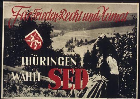 """Die SED Thüringen wirbt um Stimmen mit einem fotografischen Bildmotiv, welches genau so auch auf Plakaten für westdeutsche Heimatfilme hätte genutzt werden können. Eine jüngere Frau in trachtenähnlicher Kleidung sitzt auf einem Holzzaun oberhalb eines sonnenüberfluteten Tales, welches frei von modernen Einflüssen zu sein scheint. Hier offenbart sich, dass ältere (bürgerliche) Heimatvorstellungen durchaus noch gängig waren. Erst in den 1950er Jahren entstand mit der Idee der """"sozialistischen Heimat"""" ein Alternativprogramm.  <br /> SED-Plakat: """"Für Frieden, Recht und Heimat"""", SED Landesvorstand Thüringen, September/Oktober 1946ca. 42 x 58 cm. Quelle: Bundesarchiv Plak 100-015-038 mit freundlicher Genehmigung"""