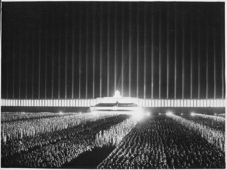 """Reichsparteitag der NSDAP in Nürnberg 1937 auf der von Scheinwerfern bestrahlten Zeppelinwiese in Nürnberg: """"Großer Appell der Politischen Leiter"""". Fotograf: unbekannt, Quelle: National Archives and Records Administration / [https://commons.wikimedia.org/wiki/File:Reichsparteitag._Der_grosse_Appell_der_Politischen_Leiter_auf_der_von_Scheinwerfern_berstrahlten_Zeppelinwiese_in..._-_NARA_-_532605.tif  Wikimedia Commons], Lizenz: public domain"""