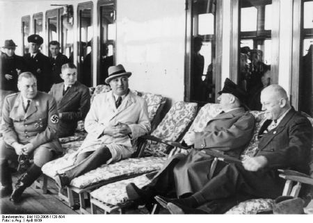 "Der ""Führer"" und sein Adlatus Robert Ley im April 1939 an Bord des KdF-Schiffes ""Robert Ley"". Links außerdem Wilhelm Brückner (Chefadjutant Hitlers), rechts Adolf Wagner (NSDAP-Gauleiter für München-Oberbayern). Fotograf: unbekannt, Quelle: [https://commons.wikimedia.org/wiki/File:Bundesarchiv_Bild_183-2006-1128-504,_KdF-Schiff_%22Robert_Ley%22,_Adolf_Hitler_an_Bord.jpg Wikimedia Commons / Bundesarchiv, Bild 183-2006-1128-504], Lizenz: [https://creativecommons.org/licenses/by-sa/3.0/de/deed.en CC-BY-SA 3.0]"