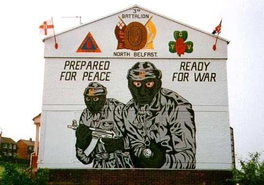 Noch heute erinnern die Murals in Belfast an den Nordirland-Konflikt. Dieses Wandgemälde mit den Paramilitärs der Ulster Volunteer Force wurde 2004 aufgenommen. (Wikimedia Commons, Lasse1974, Glenbryne, CC0 1.0)