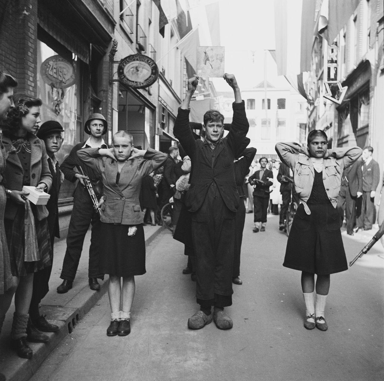 11. April 1945, Deventer: Festgenommene Mitglieder der »Nationaal-Socialistische Beweging in Nederland« (NSB) und kahlgeschorene »Moffenmeiden« werden von niederländischen Widerstandskämpfern durch die Straßen geführt. (Wikimedia Commons, Willem van de Poll, Kaalgeschoren moffenmeiden, CC BY-SA 3.0 NL)