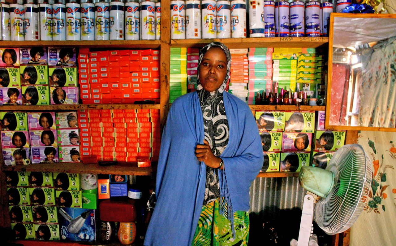 Diese Frau, die 2008 aus Somalia nach Kenia geflüchtet ist, betreibt im Lagerkomplex Dadaab einen Schönheitssalon. Im Jahr des Fotos, 2012, leben in Dadaab nach Angaben des UNHCR weit über 400.000 Menschen – manche von ihnen schon seit Anfang der 1990er-Jahre. In solchen großen Agglomerationen sind im Laufe der Zeit eigene Ökonomien und soziale Infrastrukturen entstanden. Inzwischen ist die Zahl der Bewohner/innen von Dadaab gesunken, aber viele Menschen können oder wollen nicht nach Somalia zurückkehren.(Wikimedia Commons, Oxfam East Africa, Inside the beauty salon (7550608684), CC BY 2.0)