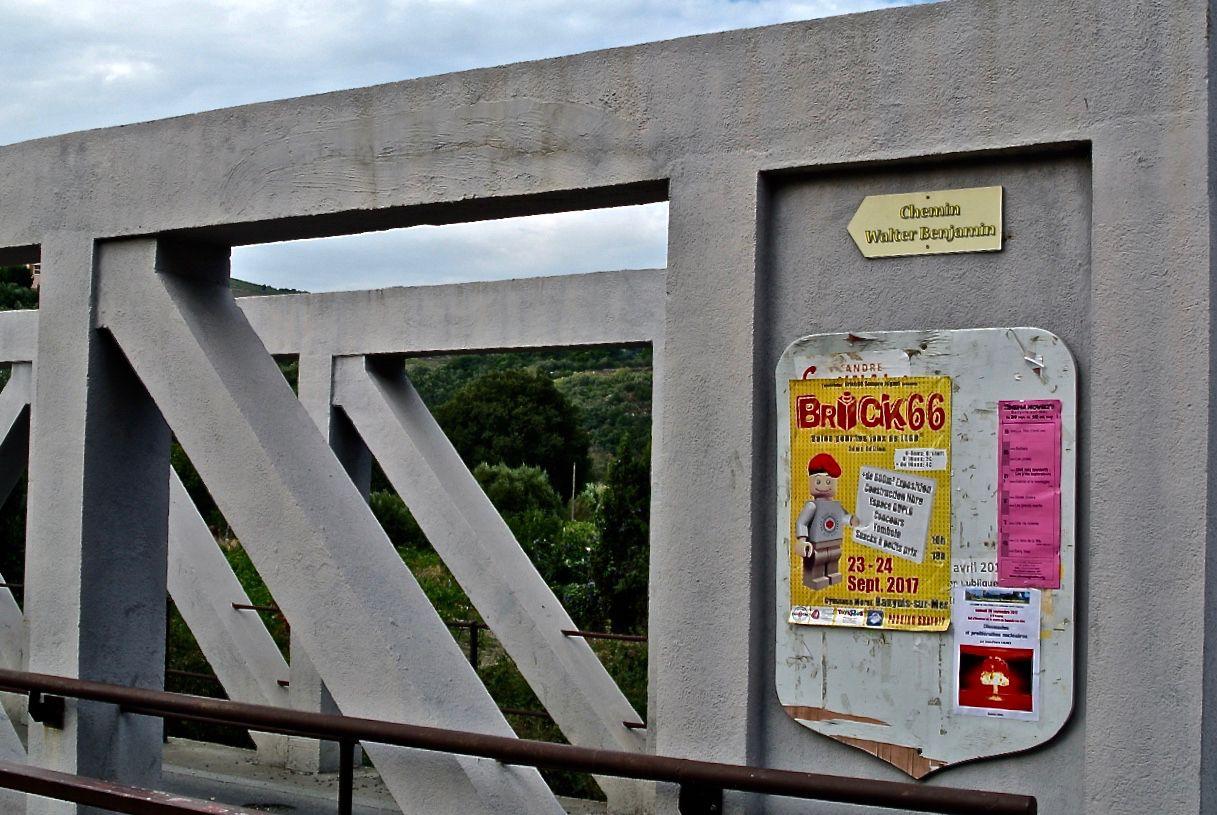In Banyuls-sur-Mer biegt der Chemin Walter Benjamin in den Vorort Puig del Mas ab. Das Erinnern an eine Flucht vor 77 Jahren und die LEGO-Messe »Brick 66« koexistieren auf der Anschlagtafel.(Foto: Verena Boos)