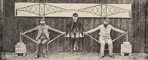 """Technikunfälle beschäftigten die europäische Öffentlichkeit: """"Tand, Tand, ist das Gebild' von Menschenhand"""", dichtete Theodor Fontane, als 1879 die Eisenbahnbrücke über den Firth of Tay vor der schottischen Ostküste mit einem Personenzug einstürzte. Der 1890 eröffnete Neubau einer Brücke entlang der gleichen Bahnstrecke musste deshalb auch technische Sicherheit demonstrieren. Auf der Fotografie illustrieren der Ingenieur Benjamin Baker und seine Mitarbeiter das Konstruktionsprinzip ihrer Brücke über den Firth of Forth bei Edinburgh.  Quelle: [https://publicdomainreview.org/collections/the-forth-bridge-building-an-icon/ National Library of Scotland, Fotosammlung], Lizenz: public domain"""