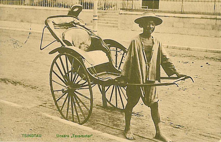 """Postkarte aus der deutschen Kolonie Tsingtau (heute Qingdao) in China, ca. 1914. Die Rikscha kann in Anschluss an David Edgerton als eine """"creole technology"""" gedeutet werden, die lokale Technikanpassung und Techniknutzung erschließen lassen. Hier macht die Bildunterschrift """"Unsere 'Taxameter'"""" deutlich, wie koloniale Machtverhältnisse in technische Alltagsnutzungen eingeschrieben waren. Quelle: [https://de.wikipedia.org/wiki/Datei:Tsingtau_Taxameter_1914.jpg Wikimedia Commons], Lizenz: public domain"""
