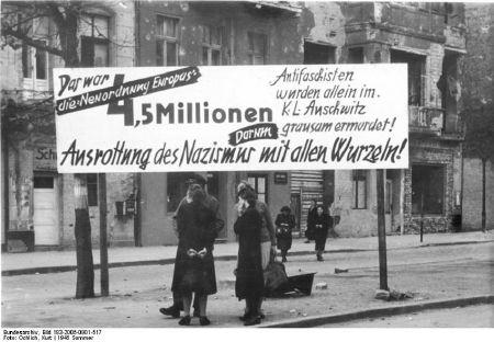 """Transparent: """"Das war die Neuordnung Europas. 4,5 Millionen Antifaschisten wurden allein im KL Auschwitz grausam ermordet! Darum Ausrottung des Nazismus mit allen Wurzeln"""", Berlin-Neukölln, Hermannstraße, Ecke Warthestraße, 21. Juni 1945. Foto: Kurt Ochlich, Quelle: [https://commons.wikimedia.org/wiki/File:Bundesarchiv_Bild_183-2005-0901-517,_Berlin-Neuk%C3%B6lln,_Anti-NS-Transparent.jpg#/media/File:Bundesarchiv_Bild_183-2005-0901-517,_Berlin-Neuk%C3%B6lln,_Anti-NS-Transparent.jpg Bundesarchiv Bild 183-2005-0901-517 / Wikimedia-Commons], Lizenz: [https://creativecommons.org/licenses/by-sa/3.0/de/deed.en CC BY-SA 3.0]"""