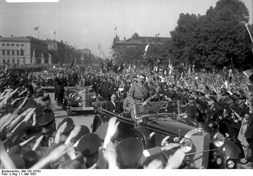 """Wächst die Bewegung und gelangt der """"Führer"""" schließlich an die Macht, kommt zum inneren Kreis eine viel weiter ausgreifende """"Gemeinde"""" hinzu, die der """"charismatischen Mission"""" des """"Führers"""" erliegt und tendenziell die gesamte Gesellschaft oder doch mindestens große Teile derselben umfassen kann. <br />Adolf Hitler und Franz von Papen am 1. Mai 1933 im Lustgarten in Berlin. Fotograf: unbekannt, Quelle: [https://commons.wikimedia.org/wiki/File:Bundesarchiv_Bild_102-15783,_Berlin,_Lustgarten,_Maikundgebung.jpg Bundesarchiv, Bild 102-15783 / Wikimedia Commons], Lizenz: [https://creativecommons.org/licenses/by-sa/3.0/de/deed.en CC-BY-SA 3.0]"""