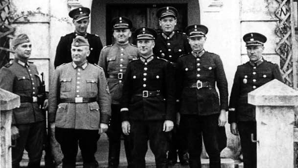 """Polnische """"Blaue"""" Polizisten und deutsche Ordnungspolizei. Die polnische Hilfspolizei, die aufgrund ihrer Uniformen """"Blaue"""" Polizei genannt wurde, war auf Befehl des Generalgouverneurs Hans Frank aus Mitgliedern der Vorkriegspolizei Polens gebildet worden. Die ca. 10.000 Männer wurden bei der Bekämpfung von Kriminalität und Schwarzhandel eingesetzt, wirkten aber auch bei der Bewachung von Ghettos, bei den Deportationen von Juden in die Vernichtungslager und bei Erschießungen mit. Fotograf: unbekannt, Quelle: [https://commons.wikimedia.org/wiki/File:Polish_police_and_orpo.jpg Wikimedia Commons/Haaretz], Lizenz: [https://creativecommons.org/licenses/by-sa/4.0/deed.en CC BY-SA 4.0]"""
