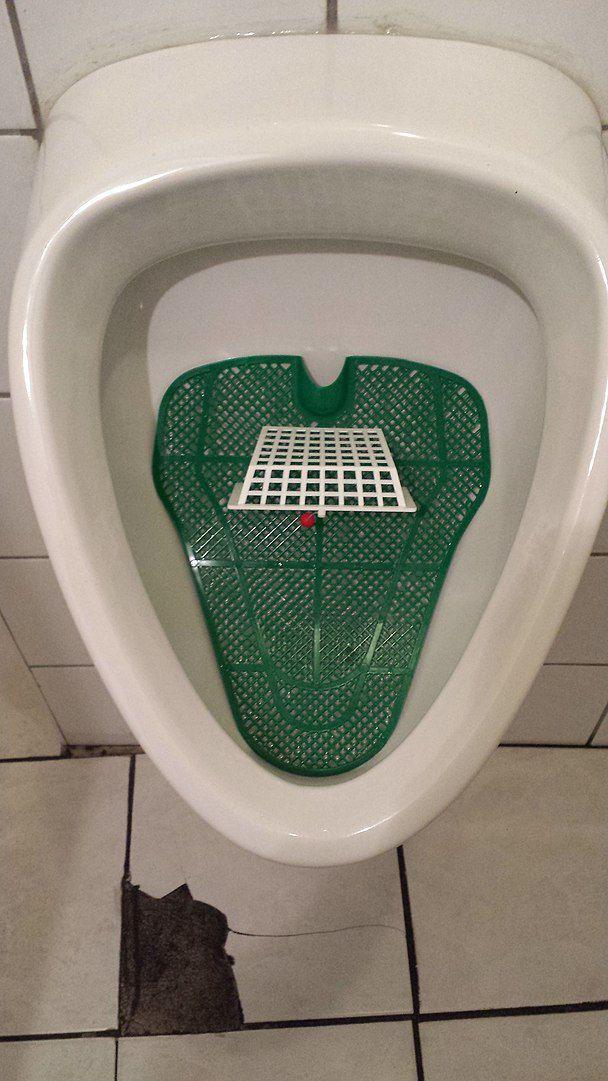 Mit der verhaltensökonomischen Technik des Nudging wird das Verhalten von Menschen in eine gewünschte Richtung gelenkt. Der Nudge (engl. Schubs, Stups) wird hier am Beispiel eines Urinals dargestellt, das mit einem Fußballfeld ausgestattet ist. Auf diese Weise wird der Nutzer zum Urinieren in das Fußballtor animiert und weniger Urin landet auf dem Boden. Grafik: WissensDürster, Quelle: [https://commons.wikimedia.org/wiki/File:Nudge_Urinal.jpg#/media/File:Nudge_Urinal.jpg Wikimedia Commons], Lizenz: [https://creativecommons.org/licenses/by-sa/4.0/deed.en CC BY-SA 4.0]