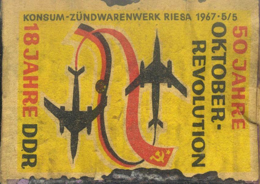 Zündholzschachtel, Konsum-Zündwarenwerk Riesa, 1967. Foto: Andreas Ludwig, 2011, Lizenz: [https://creativecommons.org/licenses/by-sa/3.0/deed.de CC BY-SA 3.0] <br /> In Zeiten des Einwegfeuerzeugs und des Gasanzünders ist das Zündholz (vulgo: Streichholz) überflüssig geworden und überlebt vor allem als überlanges Exemplar mit Ambiente-Charakter. Als Massenprodukt des 19. und 20. Jahrhunderts diente seine Verpackung als Werbeträger und Markenzeichen. Aufgrund der Vielfalt und der teilweise professionellen grafischen Gestaltung wurden Zündholzetiketten zum beliebten, vergleichsweise billigen Sammelobjekt. Das hier gezeigte Zündholzetikett trägt eine politische Botschaft: Als Teil einer Serie zum 50. Jahrestag der Oktoberrevolution wurden die DDR und der 18. Jahrestag ihres Bestehens zum Anlass genommen, beide Ereignisse im Sinne einer gemeinsamen sozialistischen historischen Tradition zusammenzubinden und damit die Botschaft einer sozialistischen Moderne in Form völkerverbindender Düsenflugzeuge zu transportieren. Ein Blick auf das Etikett verrät auch den Hersteller, das Konsum-Zündwarenwerk in Riesa, und hier setzt eine weitere Verlustgeschichte an. Das 1923 von den Konsumgenossenschaften zur Versorgung der Bevölkerung mit Basisprodukten des täglichen Bedarfs gegründete Werk war Europas größte Zündwarenfabrik. Dies galt auch für die Versorgung der DDR. 1974 beschloss die Regierung, die Riesaer Fabrik mit einer weiteren in Coswig zusammenzulegen und zu verstaatlichen.