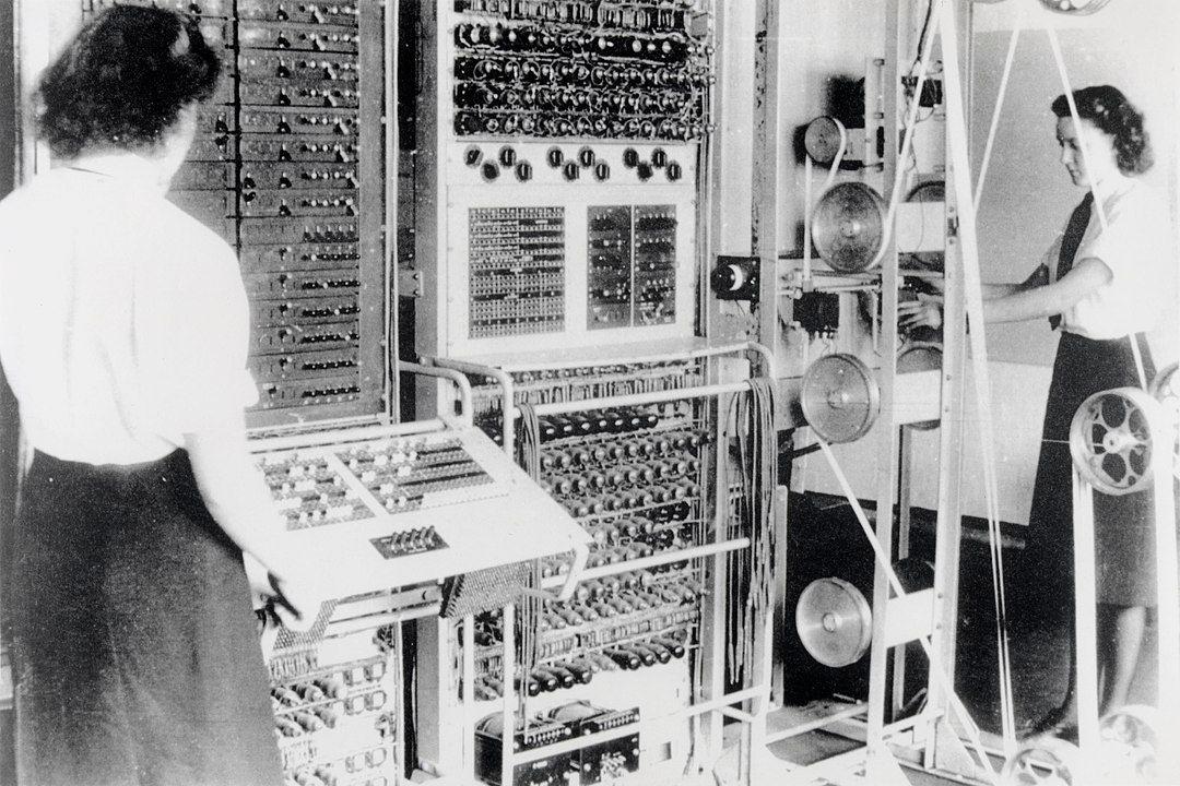 """Zwei Angehörige des britischen """"Women's Royal Naval Service"""", Dorothy Du Boisson (links) und Elsie Booker (rechts), an einem Colossus Mark II in Bletchley Park im Jahre 1943. Bei """"Colossus"""" handelte es sich um einen der weltweit ersten Röhrencomputer, der zur Dechiffrierung des Fernschreibverkehrs deutscher militärischer Kommandostellen entwickelt worden war. """"Bletchley Park"""", im Zweiten Weltkrieg Sitz des britischen Dechiffrier-Dienstes (der Government Code and Cypher School) steht in Großbritannien als Erinnerungsort für den Sieg des britischen Intellekts gegen die brutale deutsche Kriegsmaschine. Weniger Beachtung hat der Umstand gefunden, dass es sich bei den Tausenden von Personen, die in B.P. eingesetzt waren, mehrheitlich um Frauen handelte, deren Platz auch in der Intelligence History insgesamt stark unterbelichtet ist. Foto: unbekannt, Quelle: [https://commons.wikimedia.org/wiki/File:Colossus.jpg Wikimedia Commons] / The National Archives (United Kingdom) FO850/234, public domain"""