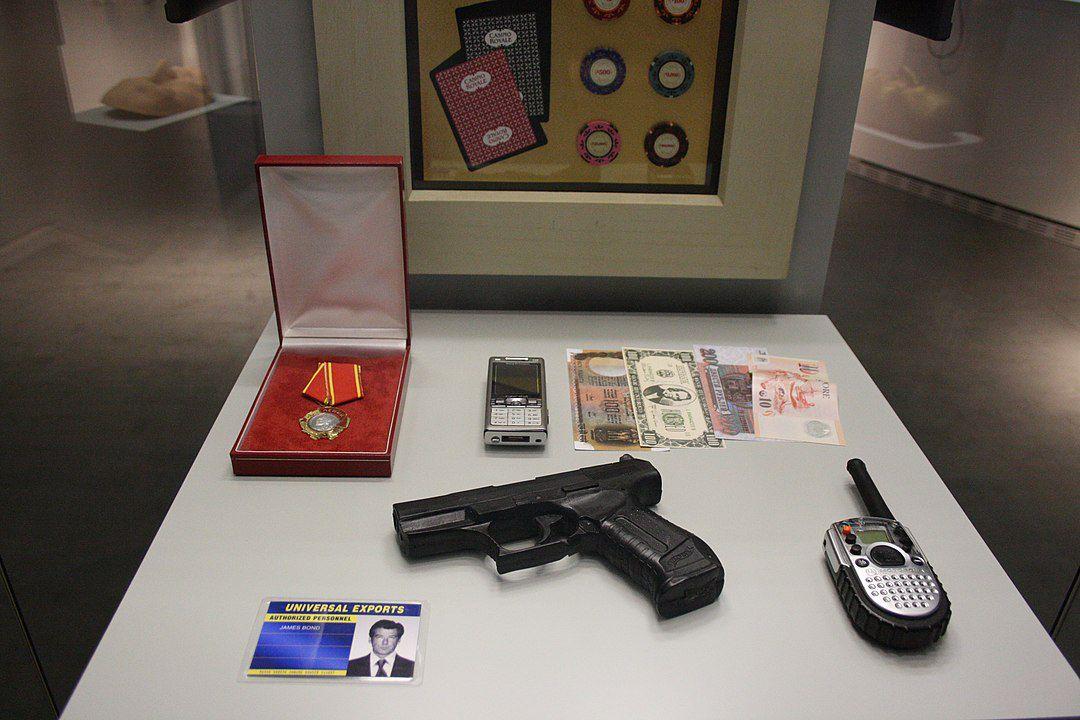 """James Bond-Requisiten im Berliner """"Spy Museum"""". Der fiktive Agent James Bond, """"007"""", illustriert paradigmatisch das Wechselverhältnis von populären Repräsentationen und nachrichtendienstlicher Praxis. Zwar wird der Kalte Krieg als historischer Bezugsraum in Ian Flemings James Bond-Romanen ebenso wie in deren Verfilmungen nur angedeutet. Sehr präsent sind hingegen Flemings Erfahrungen als Mitarbeiter des britischen Marine-Nachrichtendienstes im Zweiten Weltkrieg, als welcher er mehrfach mit der Planung von Kommandoaktionen hinter den feindlichen Linien befasst war. Dass die Perzeption von """"James Bond"""" auch politische Entscheidungsträger zu hochriskanten Unternehmungen verleitete, kann zumindest im Falle des US-Präsidenten John F. Kennedy als wahrscheinlich gelten: Als bekennender Fleming-Fan ohne eigene Erfahrungen mit Intelligence gab Kennedy etwa den Befehl zur von der CIA geplanten, von den militärischen Experten aber abgelehnten Invasion in der Schweinebucht auf Kuba, die zu einem außenpolitischen Desaster für die USA werden sollte. Foto: Scontrofrontale, 24. September 2015. Quelle: [https://commons.wikimedia.org/wiki/File:James_Bond_Requisiten.JPG#/media/File:James_Bond_Requisiten.JPG Wikimedia Commons], Lizenz: [https://creativecommons.org/licenses/by-sa/4.0/ CC BY-SA 4.0]"""