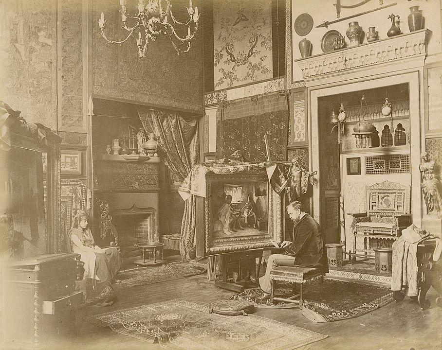 Imaginierter Orient: Der Maler Frederic Arthur Bridgman in seinem Pariser Atelier, ca. 1885. Fotograf: Edmond Bénard. Quelle: [https://library.nga.gov/discovery/fulldisplay?context=L&vid=01NGA_INST:IMAGE&search_scope=ImageCollections&tab=ImageCollections&docid=alma994147678304896 National Gallery of Art] / [https://commons.wikimedia.org/wiki/File:Frederic_Arthur_Bridgman_in_his_Paris_studio_by_Edmond_B%C3%A9nard.jpg Wikimedia Commons] ([http://en.wikipedia.org/wiki/Public_domain public domain])
