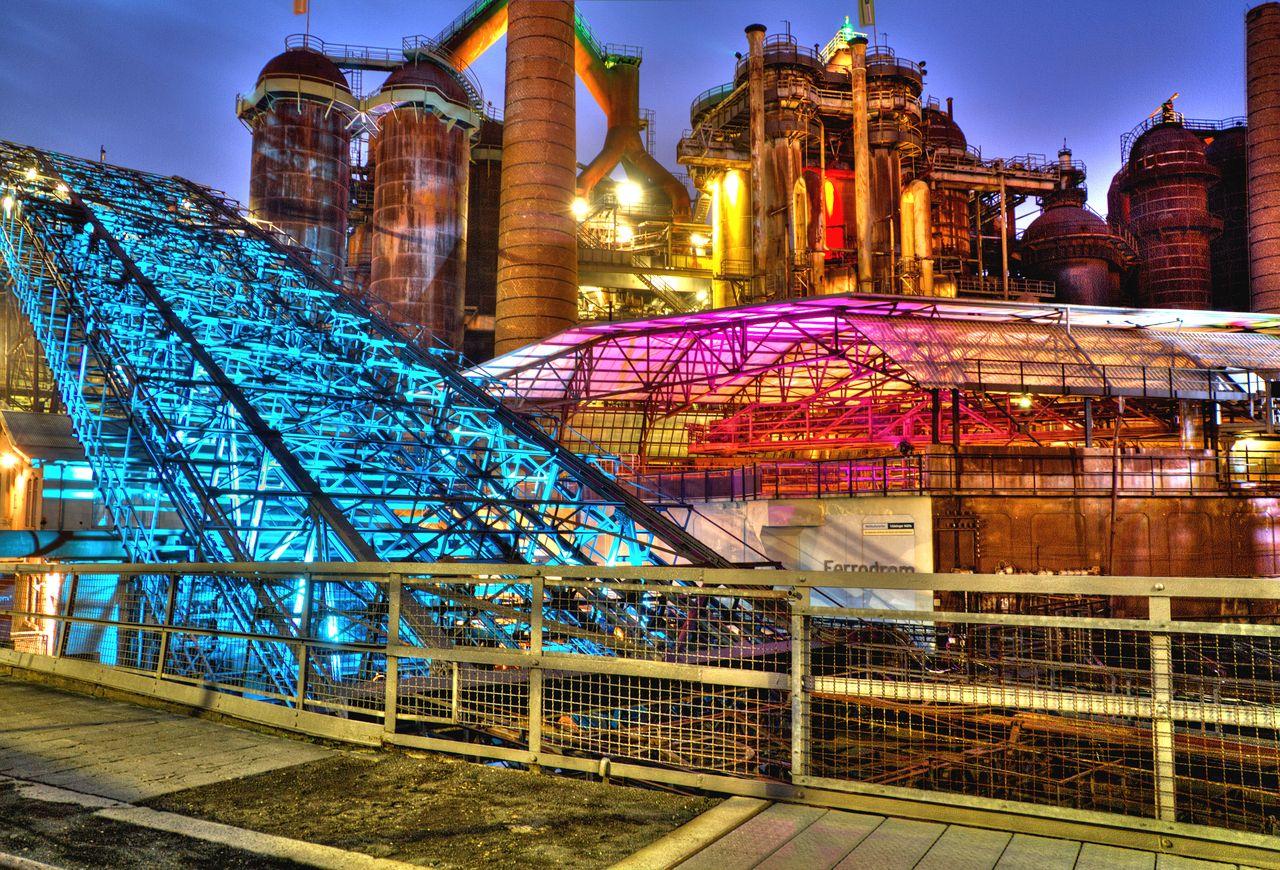 Weltkulturerbe Völklinger Hütte mit Lichtinstallation. Das Eisenwerk wurde 1986 geschlossen und 1994 in die UNESCO-Liste aufgenommen. (Wikimedia Commons, Jotha56, Hütte Völklingen, am Abend mit Beleuchtung, CC BY-SA 3.0; Foto von 2012)
