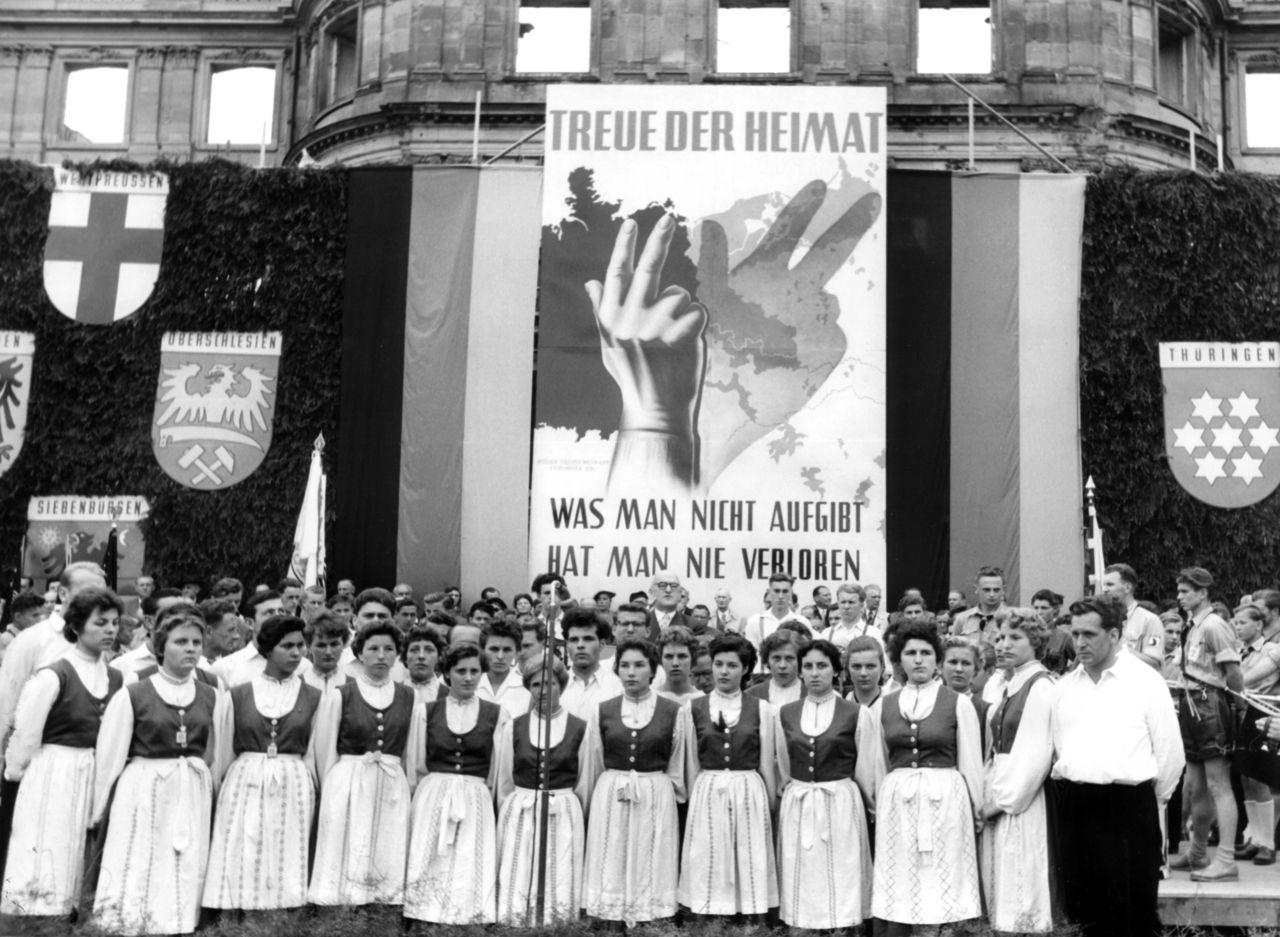 Heimatvertriebene in Stuttgart, Juli 1955: Auf einer »Treuekundgebung« füllen Trachtengruppen die Bühne, um ihre Verbundenheit mit der »verlorenen« Heimat und ihren fortdauernden Anspruch auf diese zu demonstrieren. In Polen hingegen war von den »wiedergewonnenen« Gebieten die Rede. (picture-alliance/Adolf Castagne)